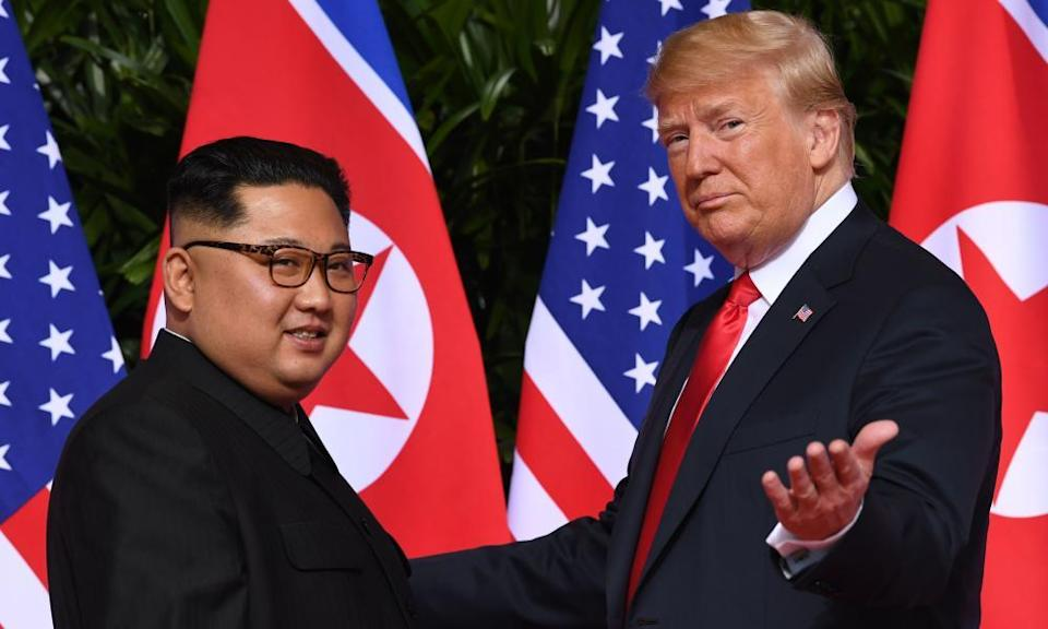 Kim Jong-un standing Donald Trump with flags in background.