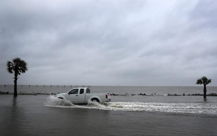 A driver navigates along a flooded road as the outer bands of Hurricane Sally come ashore in Bayou La Batre, Alabama - Joe Raedle/Getty Images