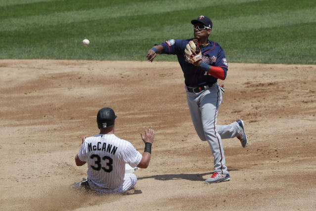Minnesota Twins shortstop Jorge Polanco, right, throws to first after forcing out Chicago White Sox's James McCann at second during the third inning of a baseball game in Chicago, Saturday, July 25, 2020. Chicago White Sox's Leury Garcia was safe at first. (AP Photo/Nam Y. Huh)