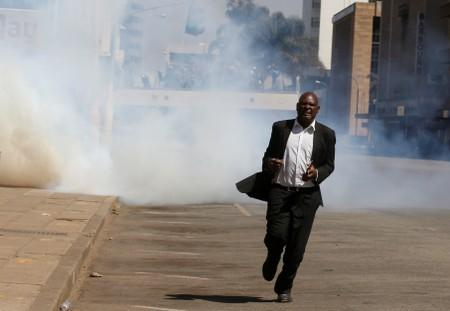 A man flees from teargas during clashes after police banned planned protests over austerity and rising living costs called by the opposition Movement for Democratic Change (MDC) party in Harare