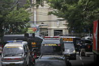 CORRECTS TO SAY ONE INSTEAD OF A FEW BOMBERS - Police vehicles are parked near a Catholic cathedral where an explosion went off in Makassar, South Sulawesi, Indonesia, Sunday, March 28, 2021. Police said at least one suicide bomber detonated outside the church on Indonesia's Sulawesi island, wounding several people. (AP Photo/Masyudi S. Firmansyah)