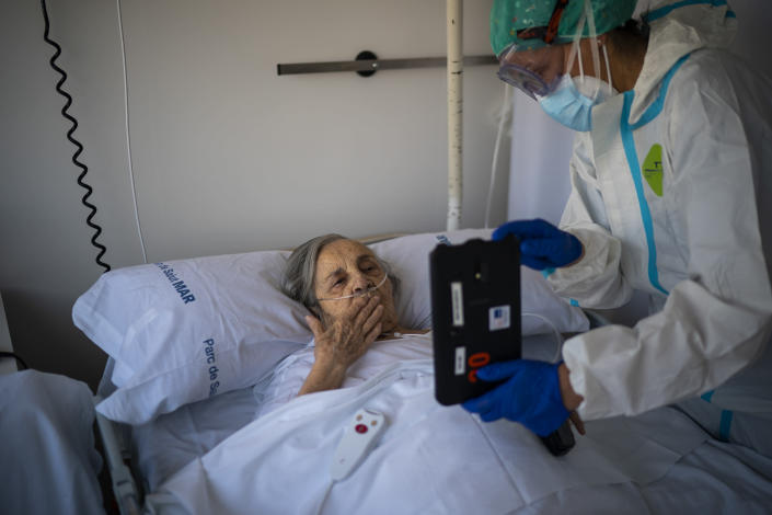 Nurse Marta Fernandez holds up a tablet computer over the chest of 94-year-old Maria Teresa Argullos Bove so that she can speak to her sister, children and grandchildren from her hospital bed at the COVID-19 ward at the hospital del Mar in Barcelona, Spain, Nov. 18, 2020. The image was part of a series by Associated Press photographer Emilio Morenatti that won the 2021 Pulitzer Prize for feature photography. (AP Photo/Emilio Morenatti)