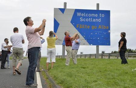 Swiss tourists take photographs next to a road that marks the England - Scotland border, at a layby on the A1 road near Berwick