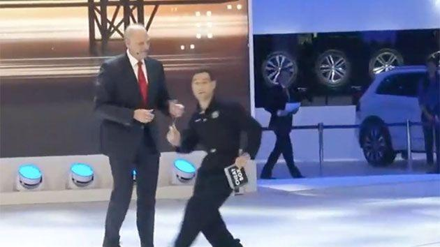 Simon Brodkin can be seen creeping up on to the stage, interrupting the VW executive talking up their newest edition. Photo: WSJ