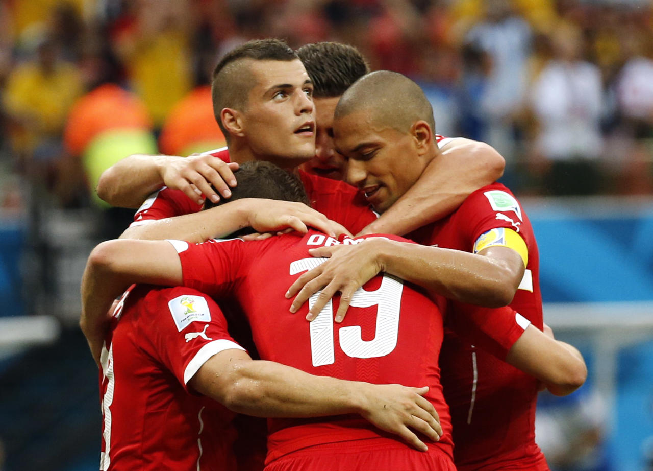 Switzerland's Xherdan Shaqiri (L, face obscured) celebrates his goal with his teammates during their 2014 World Cup Group E soccer match against Honduras at the Amazonia arena in Manaus June 25, 2014. REUTERS/Siphiwe Sibeko (BRAZIL - Tags: SOCCER SPORT WORLD CUP)