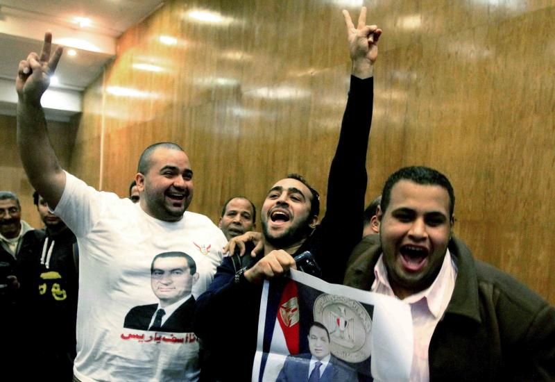 Egyptian supporters of former leader Hosni Mubarak celebrate after a court acquitted Mubarak's two sons and his last prime minister of corruption charges, judiciary officials said at a court, in Cairo, Egypt, Thursday, Dec. 19, 2013. The officials said a Cairo criminal court found Gamal and Alaa Mubarak and Ahmed Shafiq innocent of corruption in a case that arose from the 1995 sale of a plot of land to Mubarak's sons by an association led at the time by the former prime minister. (AP Photo/Ahmed Abd El Latif, El Shorouk) EGYPT OUT