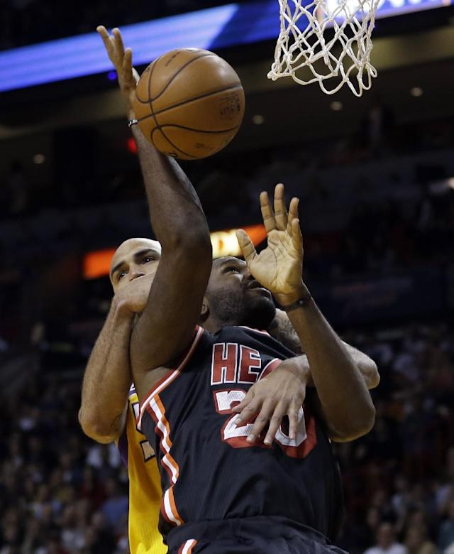 Miami Heat center Greg Oden (20) is fouled by Los Angeles Lakers center Robert Sacre (50) during the first quarter of an NBA basketball game in Miami, Thursday, Jan. 23, 2014. (AP Photo/Alan Diaz)