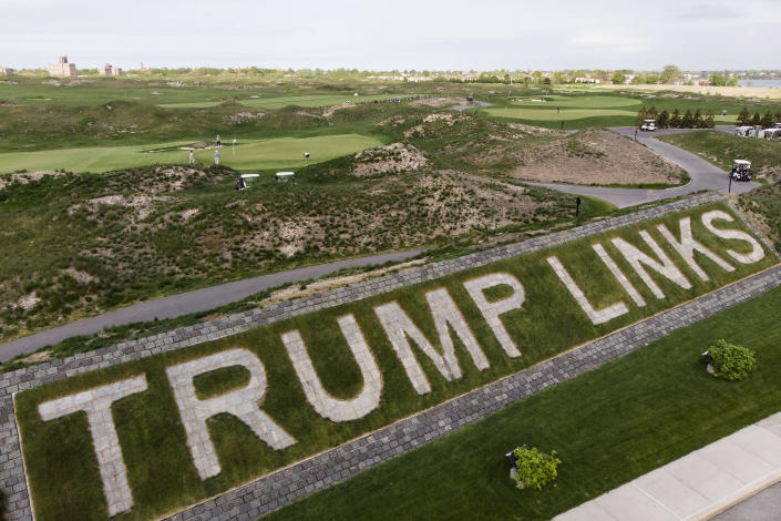 Image: Patrons play the links as a giant branding sign is displayed with flagstones at Trump Golf Links at Ferry Point in the Bronx borough of New York (John Minchillo / AP file)