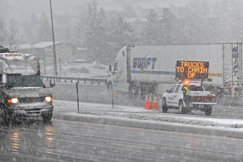 A truck moves off of Interstate I-70 to chain up before continuing eastward in Vail, Colo. on Sunday, May 11, 2014. The storm that ripped through the Vail Valley on Mother's Day caused numerous accidents and road closures. (AP Photo/The Vail Daily, Anthony Thornton)