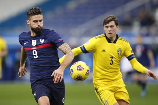 France's Olivier Giroud, left, and Sweden's Victor Lindelof go for the ball during the UEFA Nations League soccer match between France and Sweden at the Stade de France stadium in Saint-Denis, northern Paris, Tuesday, Nov. 17, 2020. (AP Photo/Francois Mori)