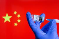 """FILE PHOTO: A woman holds a small bottle labeled with a """"Coronavirus COVID-19 Vaccine"""" sticker and a medical syringe in front of displayed China flag in this illustration"""