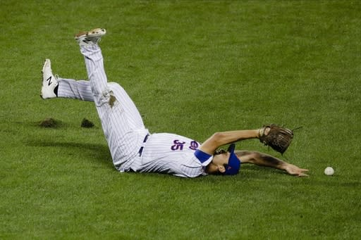 New York Mets relief pitcher Jared Hughes (35) loses control of the ball hit by Miami Marlins' Matt Joyce (7) during the eighth inning of a baseball game Friday, Aug. 7, 2020, in New York. (AP Photo/Frank Franklin II)