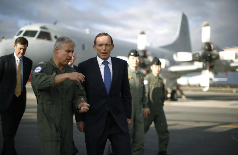 """Australian Prime Minister Tony Abbott is guided around a Royal Australian Air Force P-3C Orion aircraft by Australian Air Force Group Commander Craig Heap, second from left, during Abbott's visit to RAAF Base Pearce in Bullsbrook, near Perth, Australia, Monday, March 31, 2014. Abbott said the search for Malaysia Airlines Flight 370 is """"an extraordinarily difficult exercise"""" but that it will go on as long as possible. Abbott said Monday that although no debris has been found in the southern Indian Ocean that can be linked to the plane missing for more than three weeks, the searchers are """"well, well short"""" of any point where they would scale the hunt back. (AP Photo/Jason Reed, Pool)"""