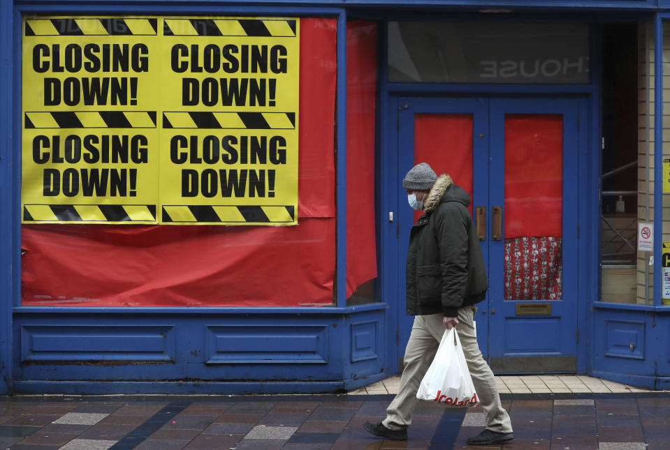 A man wearing a face mask to protect against coronavirus, walks past a closed shop in Stirling, Scotland, Sunday, Nov. 15, 2020. Scotland are currently using a tier system to try and drive down coronavirus cases. (Andrew Milligan/PA via AP)