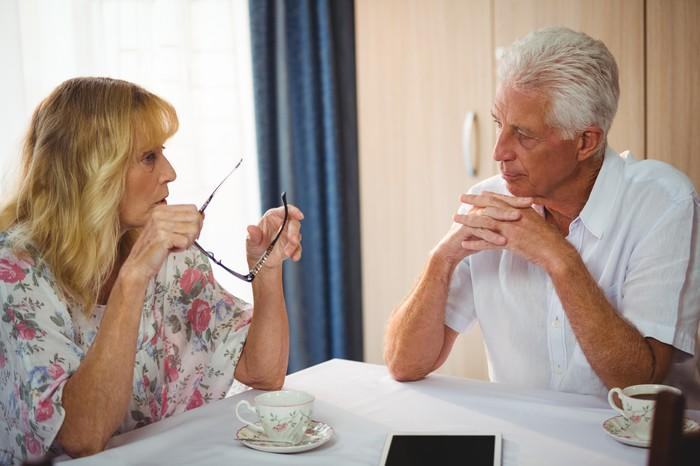Senior man and woman sitting at table with teacups in front them, both sporting serious expressions