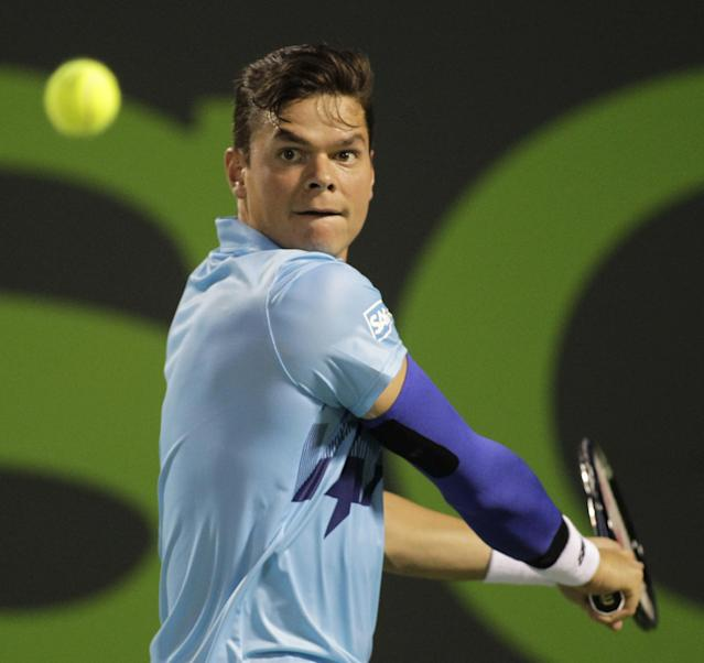 Milos Raonic, of Canada, returns the ball to Rafael Nadal, of Spain, during the Sony Open tennis tournament, Thursday, March 27, 2014, in Key Biscayne, Fla. (AP Photo/Luis M. Alvarez)