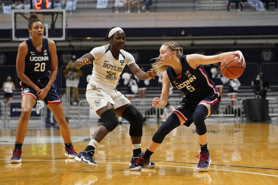 Connecticut guard Paige Bueckers (5) drives against Butler guard Upe Atosu (21) during the second quarter of an NCAA college basketball game in Indianapolis, Saturday, Feb. 27, 2021. (AP Photo/Michael Conroy)