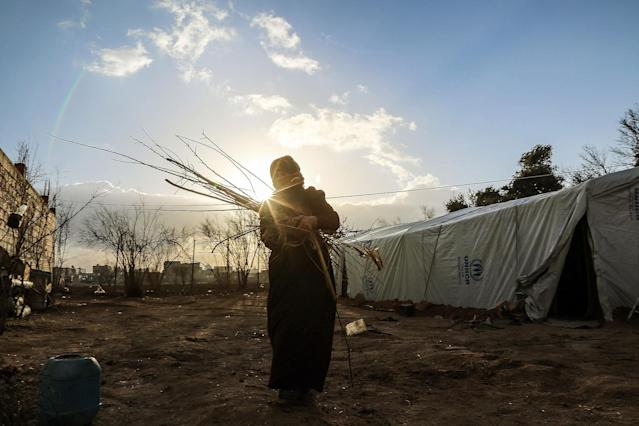 <p>An internally displaced Syrian woman, who fled from East Ghouta region as Assad Regime violates the ceasefire on ongoing civil war, carries a bundle of tree branch at a makeshift camp, relatively safer than their home neighborhoods in Damascus, Syria on Jan. 10, 2017. (Photo:Tarik al Masri/Anadolu Agency/Getty Images) </p>