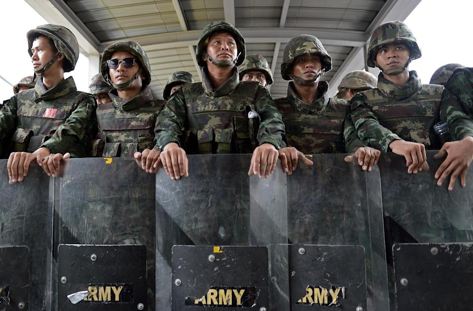 File photo shows Thai soldiers standing behind their shields after they sealed off an elevated train station leading to a shopping mall and broke up an anti-coup protest in downtown Bangkok on June 1, 2014 (AFP Photo/Christophe Archambault)