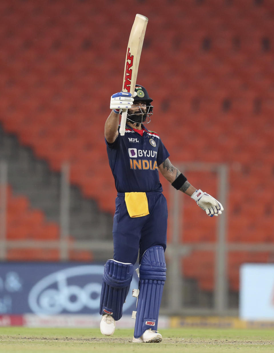 India's captain Virat Kohli raises his bat to celebrate scoring fifty runs during the fifth Twenty20 cricket match between India and England at Narendra Modi Stadium in Ahmedabad, India, Saturday, March 20, 2021. (AP Photo/Ajit Solanki)