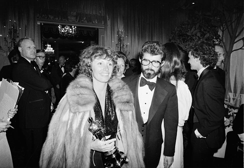 """Marcia Lucas, wife of director George Lucas, right, carries her Oscar statuette as they arrive at a post Academy Awards party at the Beverly Hilton Hotel in Los Angeles, Ca., April 4, 1978.  She won for best achievement in film editing for """"Star Wars,"""" directed by her husband.  (AP Photo)"""