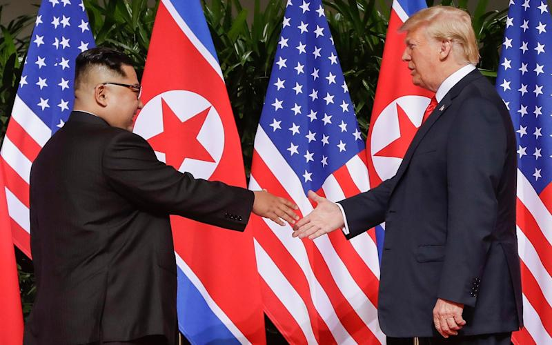 US President Donald Trump reaches to shake hands with North Korea leader Kim Jong-un in Singapore last year - AP