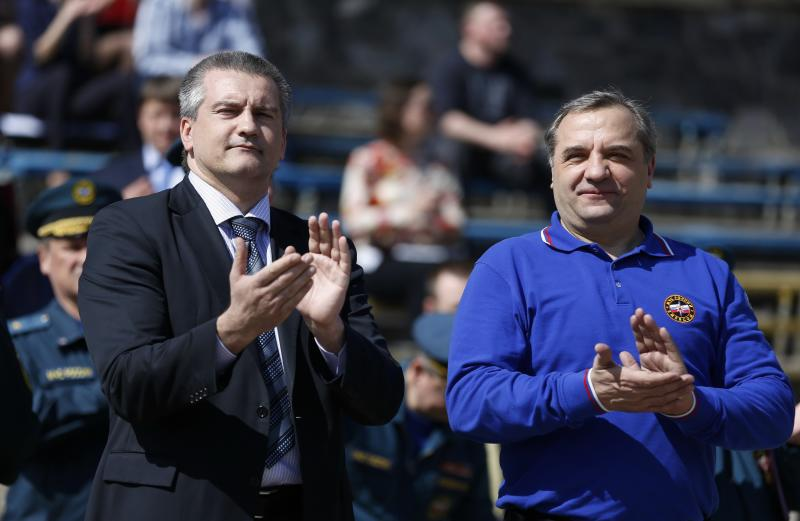 Crimean Premier Sergei Aksyonov, left, and Russian Emergency Situations Minister Vladimir Puchkov applaud at a meeting with emergency workers in Simferopol, Crimea, Tuesday, March 25, 2014. Puchkov met with local emergency officials in Simferopol and said that Russia sent diesel generators to Crimea to serve as a back-up in case of power outages. Crimea faced power cutoffs after Ukraine briefly cut energy supplies to the region. (AP Photo/Maxim Vetrov)