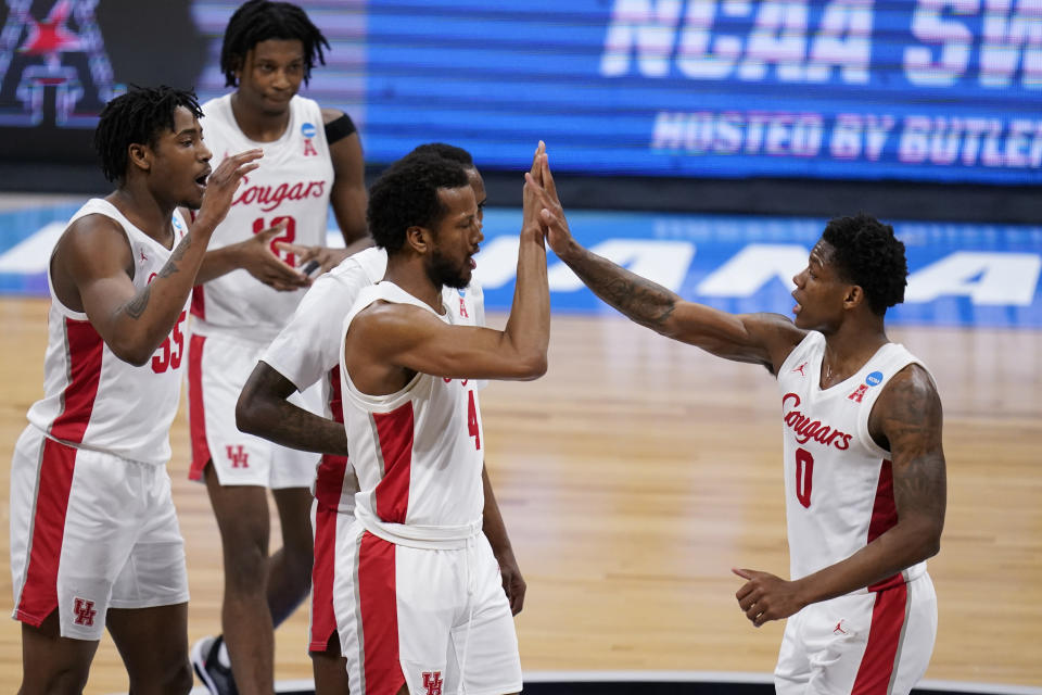 Houston forward Justin Gorham (4) and Marcus Sasser (0) celebrate a play against Syracuse in the first half of a Sweet 16 game in the NCAA men's college basketball tournament at Hinkle Fieldhouse in Indianapolis, Saturday, March 27, 2021. (AP Photo/Michael Conroy)