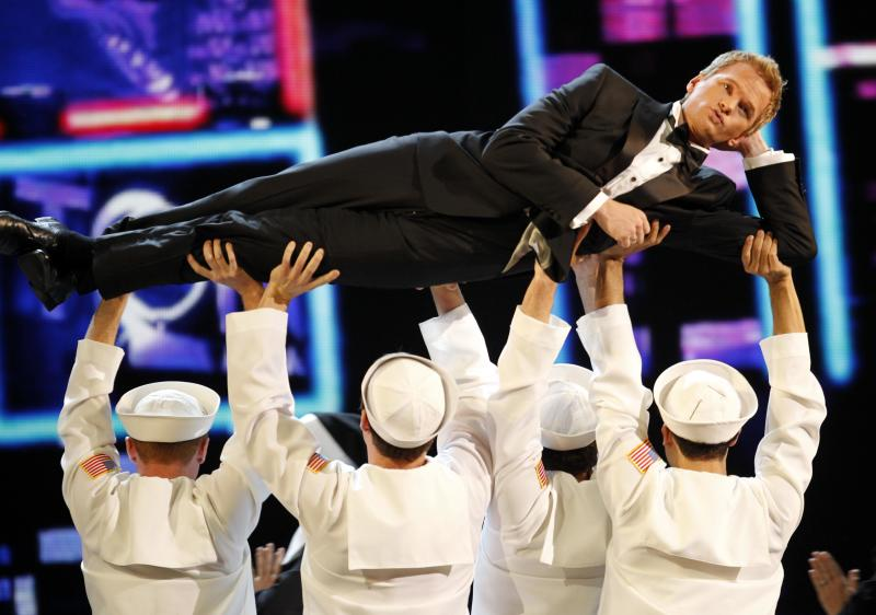 """FILE - This June 12, 2011 file photo shows host Neil Patrick Harris performing during the 65th annual Tony Awards in New York.  Harris will be back for his fourth turn as host of the Tony Awards. Producers of the show announced Thursday that Harris, a stage veteran and star of the CBS sitcom """"How I Met Your Mother,"""" will host the 67th annual awards to be presented June 9 at Radio City Music Hall in New York City. The show will air live on CBS. (AP Photo/Jeff Christensen, file)"""