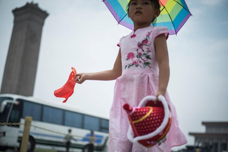 A child holds the national flag in Tiananmen Square in Beijing on June 3, 2016 (AFP Photo/Fred Dufour)