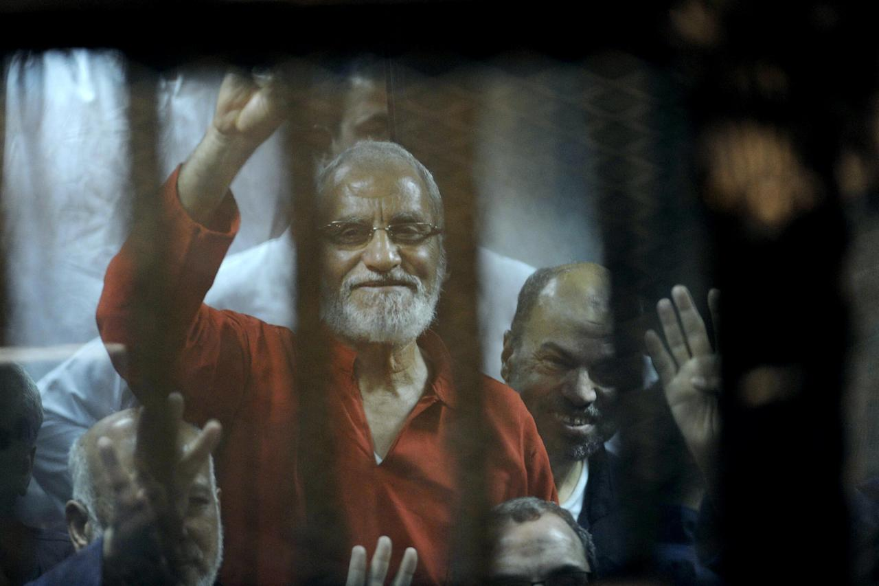 Muslim Brotherhood spiritual leader, Mohammed Badie wearing a red jumpsuit that designates he has been sentenced to death, waves from a defendants cage in a makeshift courtroom at the national police academy, eastern Cairo, Egypt, Saturday, May 16, 2015. An Egyptian court on Saturday sentenced ousted President Mohammed Morsi and over 100 others to death including Badie, as well as one of the Arab world's best known Islamic scholars, the Qatar-based Youssef al-Qaradawi. Badie was sentenced to death in another case in April. (AP Photo/Ahmed Omar)