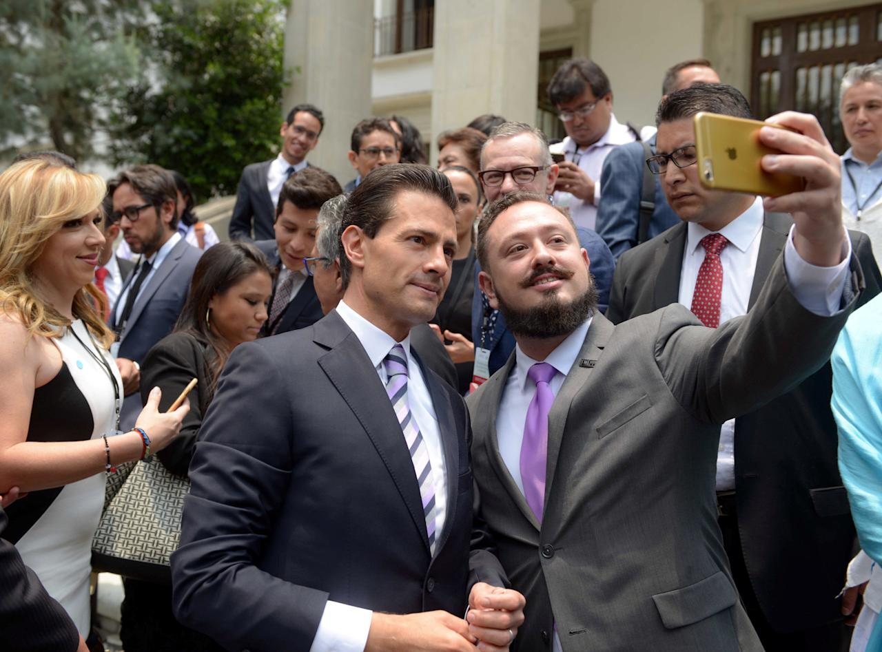 Mexican President Enrique Pena Nieto poses for a selfie with invitees after an official ceremony to mark the International Day Against Homophobia at Los Pinos presidential house in Mexico City, Mexico, May 17, 2016, in this handout provided by Mexico Presidency. Mexico Presidency/Handout via REUTERS ATTENTION EDITORS - THIS IMAGE WAS PROVIDED BY A THIRD PARTY. EDITORIAL USE ONLY.     TPX IMAGES OF THE DAY