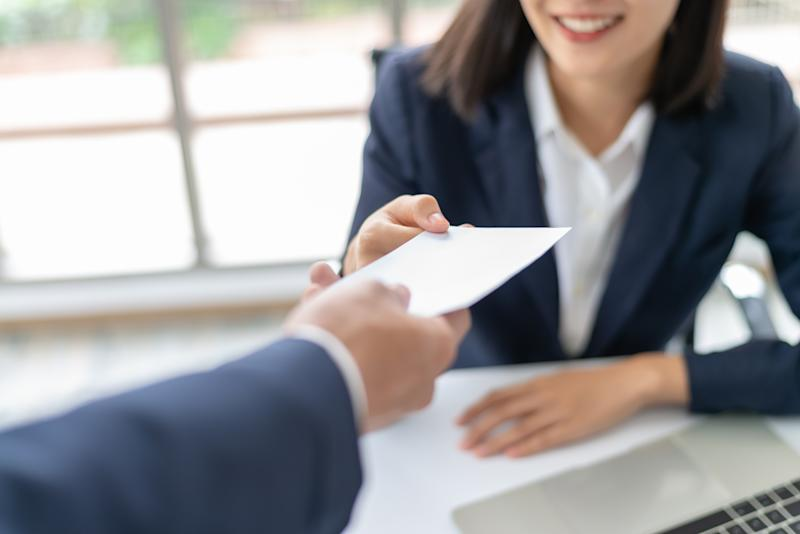 Young Asian business woman receiving salary or bonus money from boss or manager at office happily.