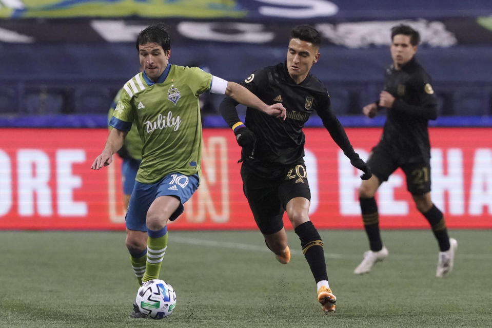 Seattle Sounders midfielder Nicolas Lodeiro (10) dribbles ahead of Los Angeles FC midfielder Eduard Atuesta during the first half of an MLS playoff soccer match Tuesday, Nov. 24, 2020, in Seattle. (AP Photo/Ted S. Warren)
