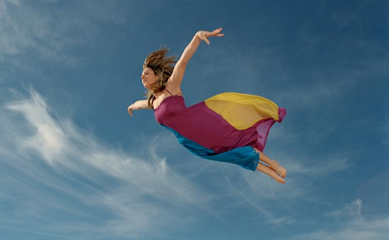 A woman flying in a red and yellow dress.