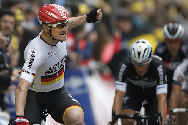 Germany's Andre Greipel looks back as he celebrates crossing the finish line ahead of fourth place Australia's Mark Renshaw, right, to win the sixth stage of the Tour de France cycling race over 194 kilometers (120.5 miles) with start in Arras and finish in Reims, France, Thursday, July 10, 2014. (AP Photo/Peter Dejong)