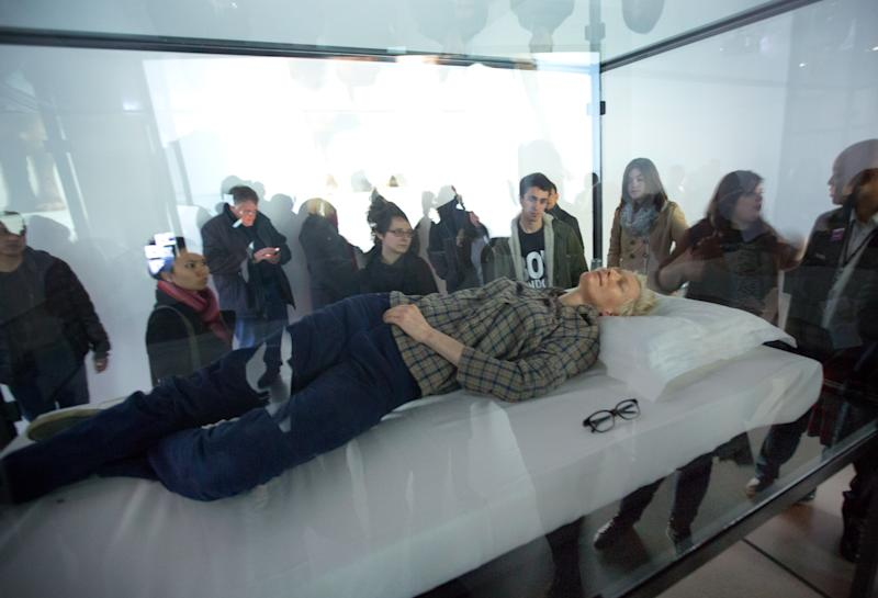 "Actress Tilda Swinton performs the art of sleeping in her one-person piece called ""The Maybe,"" in New York's Museum of Modern Art,  Monday, March 25, 2013. In ""The Maybe,"" first performed at the Serpentine Gallery in London in 1995, Swinton lies sleeping in a glass box for the day. The exhibit will move locations within the museum every time Swinton performs. (AP Photo/Richard Drew)"