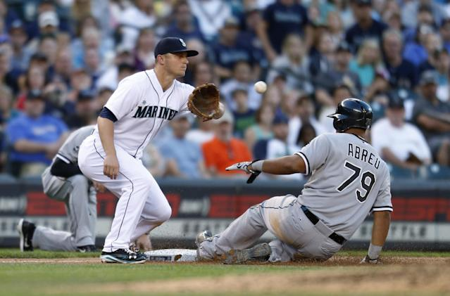 Chicago White Sox's Jose Abreu slides safely into third as Seattle Mariners third baseman Kyle Seager takes the throw during the seventh inning of a baseball game in Seattle on Saturday, Aug. 9, 2014. (AP Photo/John Froschauer)