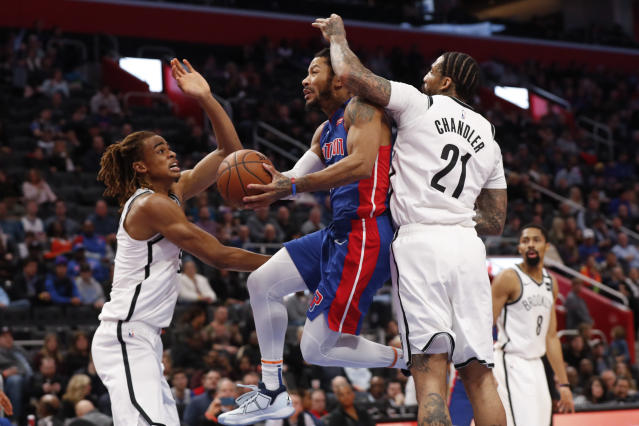 Detroit Pistons guard Derrick Rose, center, drives between Brooklyn Nets forward Nicolas Claxton, left, and Wilson Chandler (21) in the second half of an NBA basketball game in Detroit, Saturday, Jan. 25, 2020. (AP Photo/Paul Sancya)