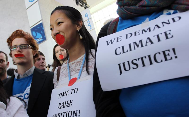 Local and international activists march inside a conferences center  to demand urgent action to address climate change at the U.N. climate talks in Doha, Qatar, Friday, Dec.7, 2012. A dispute over money clouded U.N. climate talks Friday, as rich and poor countries sparred over funds meant to help the developing world cover the rising costs of mitigating global warming and adapting to it. (AP Photo/Osama Faisal)