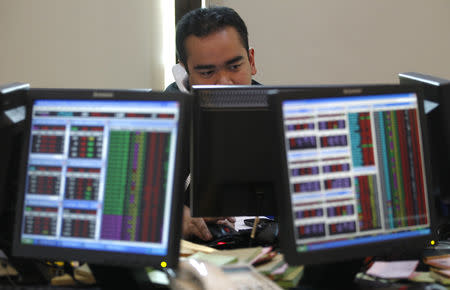 An Indonesian broker speaks on his phone while monitoring the share price at Bank Mandiri Sekuritas trading floor in Jakarta August 19, 2011. REUTERS/Supri/Files