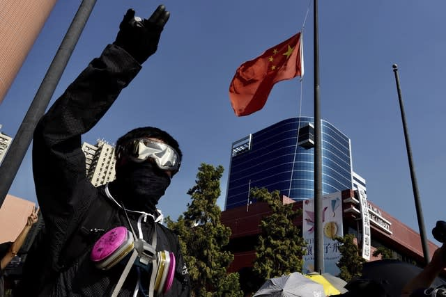 A protester lowers a Chinese flag which was later burned