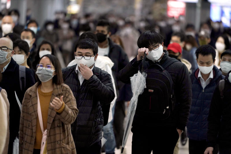 FILE - In this April 20, 2020, file photo, a station passageway is crowded with face mask wearing commuters during a rush hour, in Tokyo. When the Japanese government declared an emergency to curb the spread of the coronavirus earlier April and asked people to work from home, crowds rushed to electronics stores. Many Japanese lack the basic tools needed to work from home. Contrary to the ultramodern image of Japan Inc. with its robots, design finesse and gadgetry galore, in many respects the country is technologically challenged. (AP Photo/Eugene Hoshiko, File)