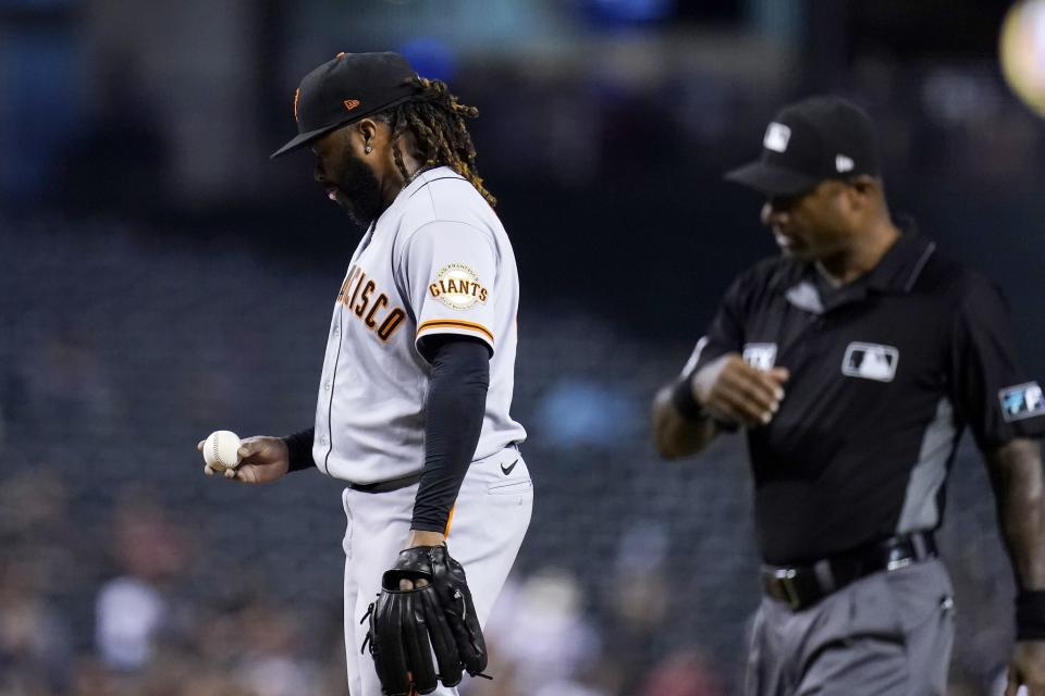 San Francisco Giants starting pitcher Johnny Cueto, left, looks at the baseball after being called for a balk as umpire Alan Porter looks on during the second inning of the team's baseball game against the Arizona Diamondbacks, Tuesday, Aug. 3, 2021, in Phoenix. (AP Photo/Ross D. Franklin)