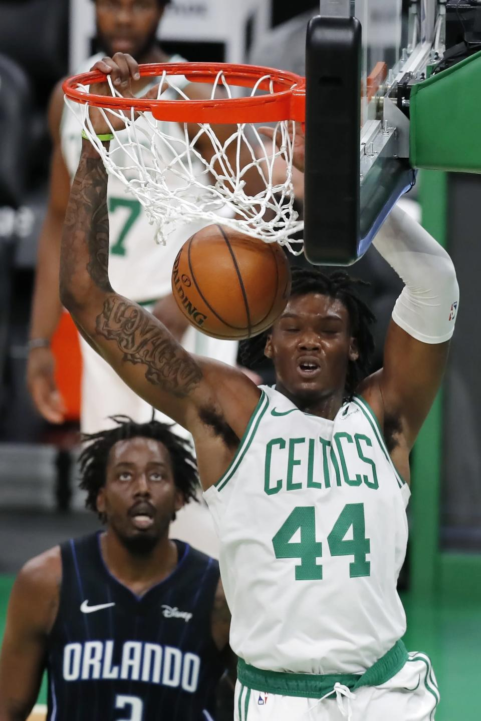 Boston Celtics' Robert Williams III (44) dunks in front of Orlando Magic's Al-Farouq Aminu during the first half of an NBA basketball game, Sunday, March 21, 2021, in Boston. (AP Photo/Michael Dwyer)