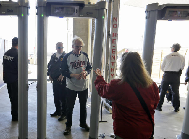 A fan is encouraged to enter Target Field through newly installed metal detectors before the Minnesota Twins host the Oakland Athletics in a home opener baseball game in Minneapolis, Monday, April 7, 2014. Only a few of the gates currently have metal detectors, but they will be installed at each gate before Minneapolis hosts the MLB All Star Game in July. (AP Photo/Ann Heisenfelt)