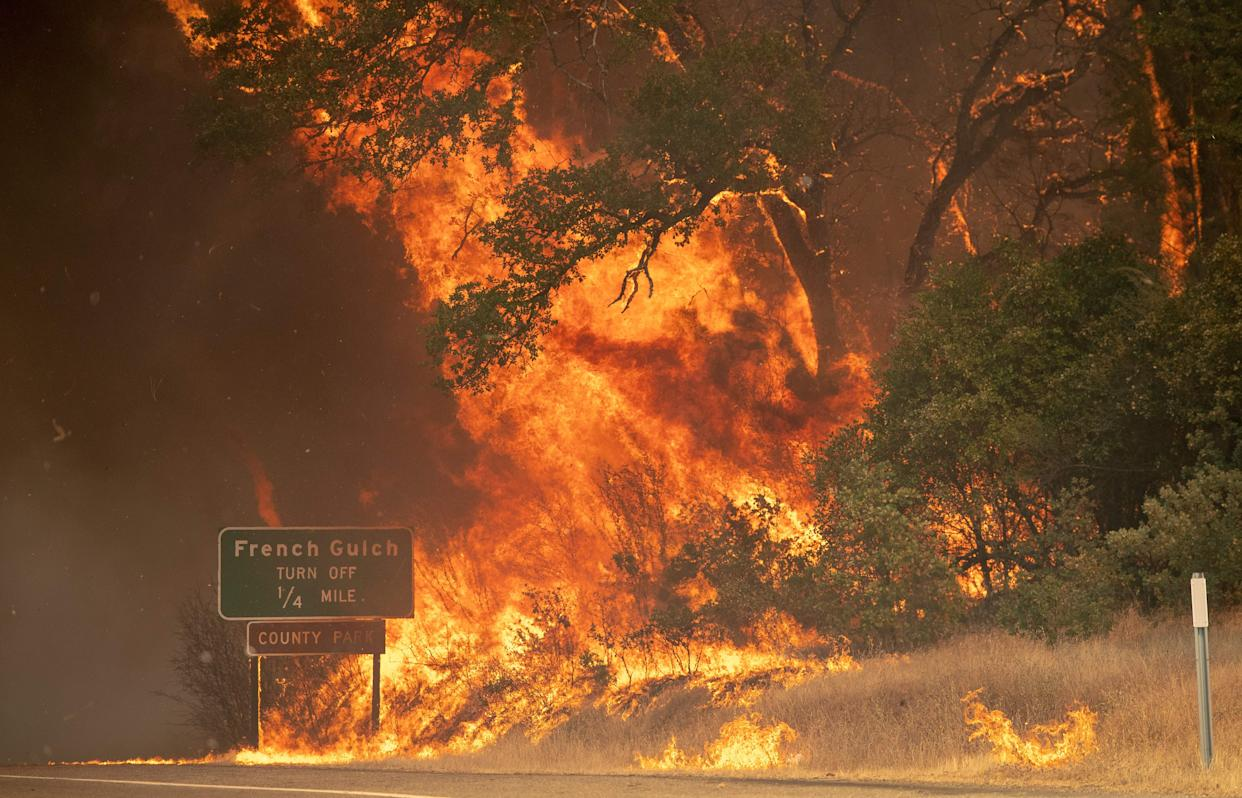 A power pole leans over a burned property as the sky turns a deep orange during the Carr fire near Redding, California on July 27, 2018.
