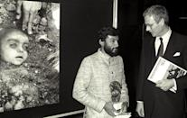 Indian photographer Pablo Bartholomew (L) poses with Dutch Foreign Minister Hans Van Den Broek in Amsterdam, April 14, 1985, after receiving an award for Best World Press Photo of 1984. Behind them is the winning entry, which shows a child victim in his native India of the Bhopal disaster, caused by a gas leak from the Union Carbide pesticide plant. Photo: Scanned from negative Reuters/E. Werner CMC