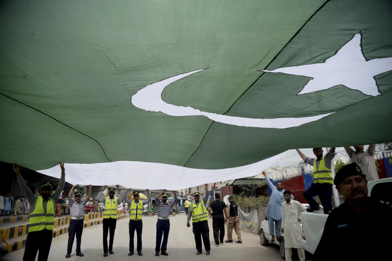 Pakistani police officers hold a national flag during a rally to mark the country's Independence Day, in Peshawar, Pakistan, Tuesday, Aug 14, 2018. The anniversary comes amid political change with a new government taking over this week following the July 25 general elections. Pakistan gained independence when British left India and split the subcontinent in 1947. (AP Photo/Muhammad Sajjad)
