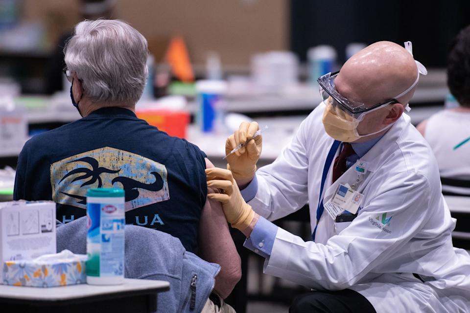Chief clinical officer John Corman, MD at Virginia Mason administers a dose of the Pfizer Covid-19 vaccine at the Amazon Meeting Center in downtown Seattle, Washington on January 24, 2021. (Photo by Grant HINDSLEY / AFP)